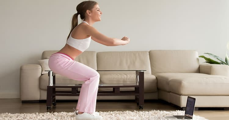 4 minute workout image of young woman squatting