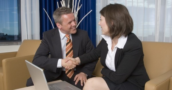 A businessman an businesswoman shaking hands