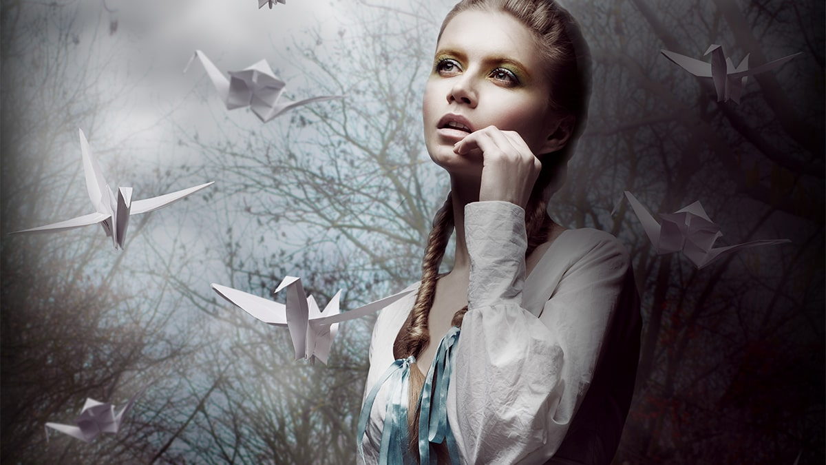 image of woman surrounded by origami birds