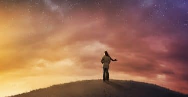 woman looking out into the universe from atop a hill