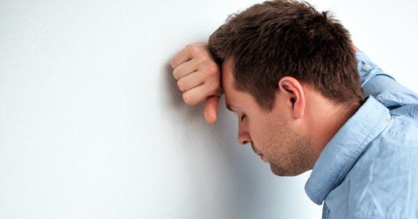 Caucasian man feeling headache or nausea.