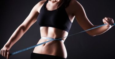 Fitness woman measuring her waist, weight loss