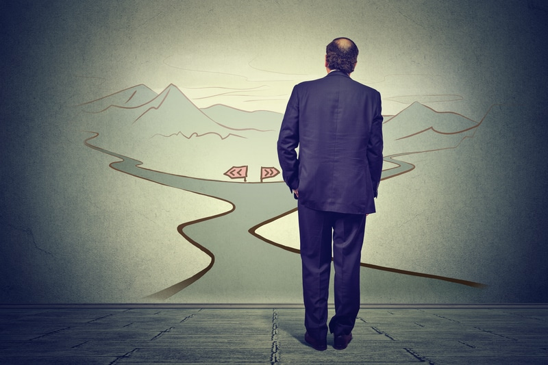 Business man in front of two roads thinking deciding