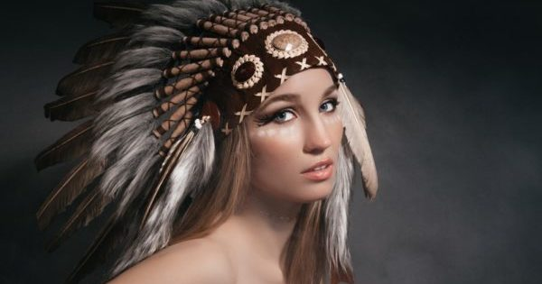 Portrait perfect woman in garb of American Indians in the smoke on a gray background. Hat made of feathers. Mysterious mystical