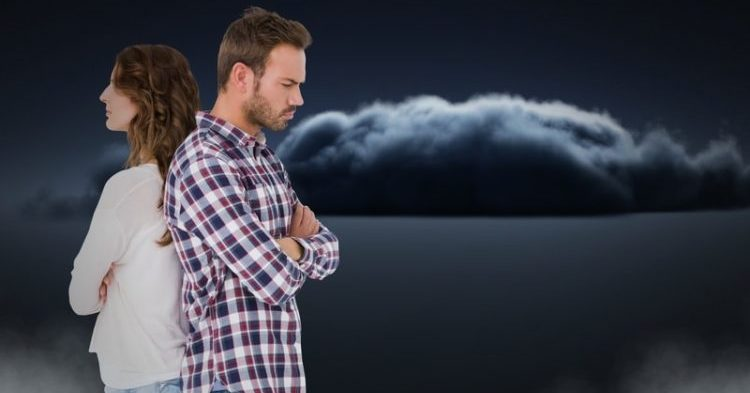 Couple facing back to back and upset with clouds