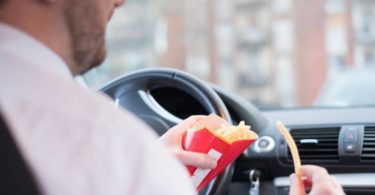 Man eating junk food and driving seated in car