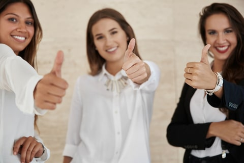 Pretty businesswomen showing thumbs up