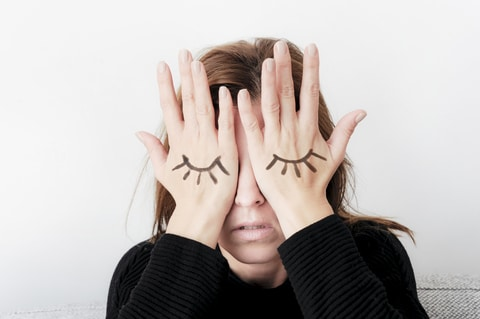 Young woman is covering her eyes with her palms. Eyes painted on her hand.