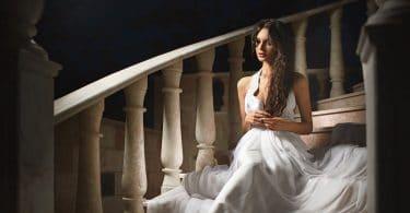 beautiful woman sitting on steps in darkened room