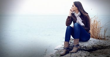 image of unhappy woman sitting by the shore
