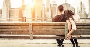 image of young couple holding hands overlooking new york sunrise