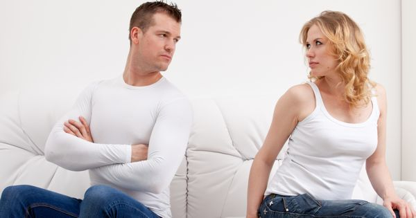 Young couple sulking after conversation sitting on sofa
