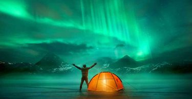 man camping with aurora borealis in background