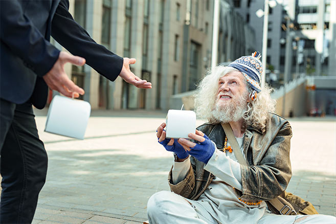 kindness quotes image of a man begging in the street with another man giving money