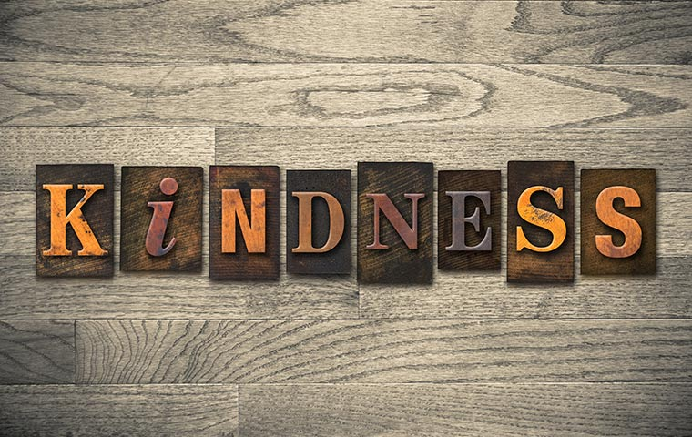 kindness quotes image of the word kindness against a wooden backdrop