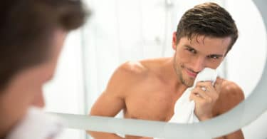 man checking himself in mirror