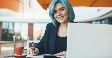 image of woman with blue dyed hair sitting writing