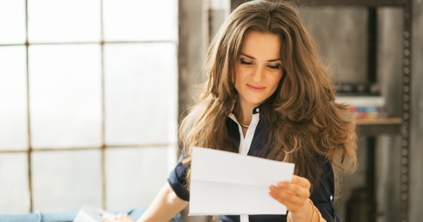 Young woman reading letter in loft apartment