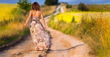 woman walking along a dirt path on a summers day