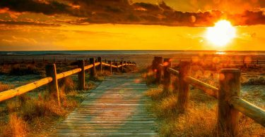 image of a boardwalk on beach at sunset