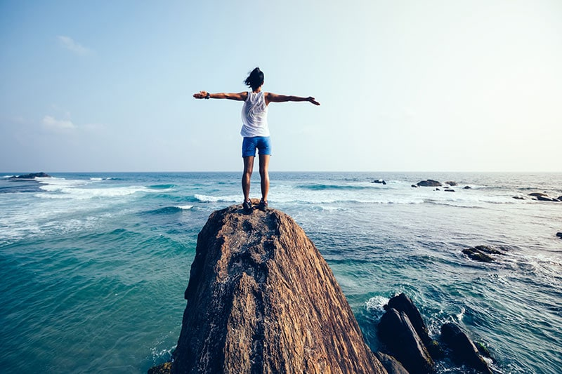 shows image of woman standing with arms outsretched on a massive rock overlooking the sea