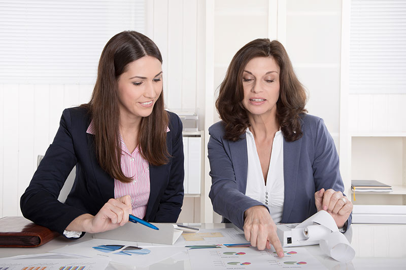 shows image of a feamle business woman showing another woman accounts