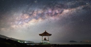 man sitting alone looking at universe skies