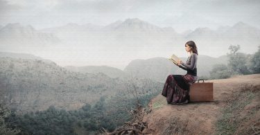 image of woman sitting alone reading a book on top of mountain