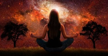 image of woman meditating against universe backdrop